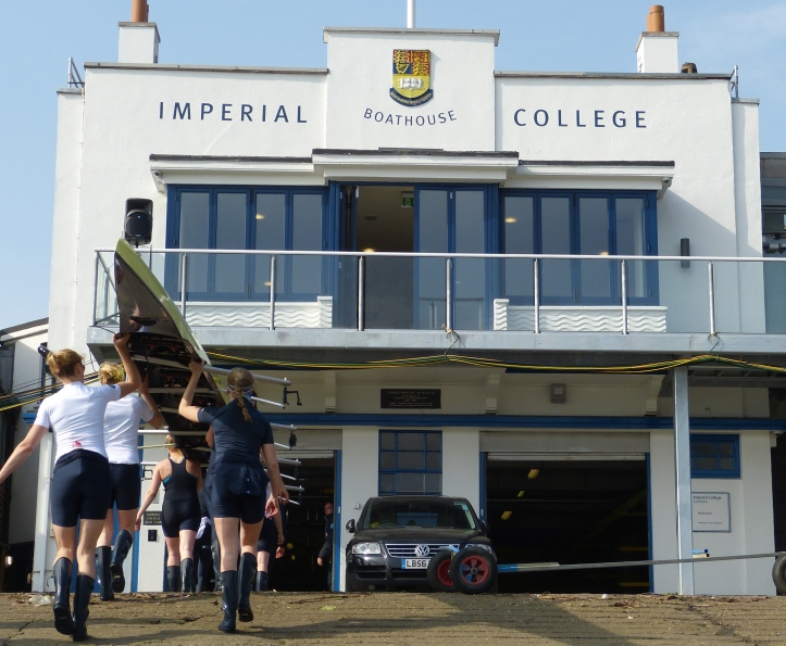 Osiris take their eight into the simple but pleasing building that is Imperial College boathouse, the base for the Oxford women during Tideway Week.