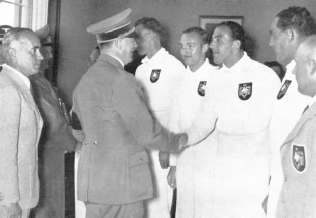 Ernst Gaber being congratulated by Adolf Hitler. The German Chancellor, who, as Patron of the Olympic Games, was present at all of the rowing competitions. He is shown congratulating the victorious German coxed four in the boat house after the final. Behind him is the Reich Sport Leader, Hans von Tschammer und Osten and to his left Hermann Göring can also be seen.