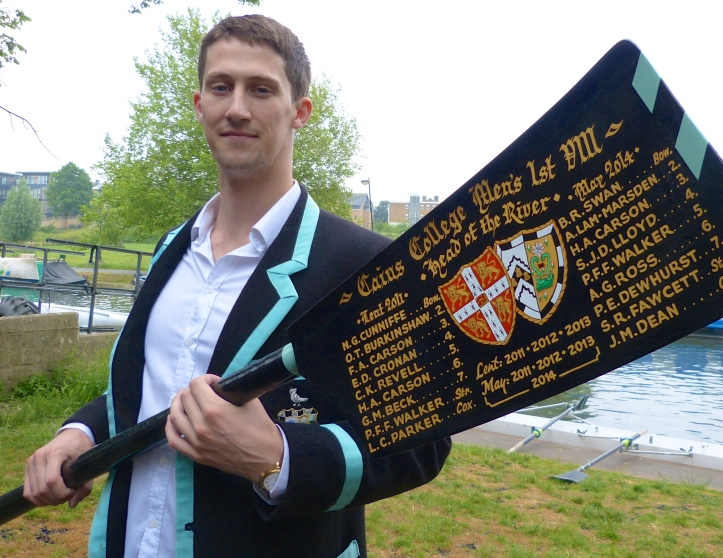 Pic 24. Hugh Carson of Caius with a possibly atypical blade, one which records his several achievements in bump racing. He is wearing a Caius Boat Club blazer, usually described as 'black with a Cambridge Blue stripe'. Legend says that the Blue stripe was added after a Caius crew beat the University crew but The Bumps says that 'the shade of blue used by Caius has….. almost certainly changed over the years to mirror the colour used by the University'.