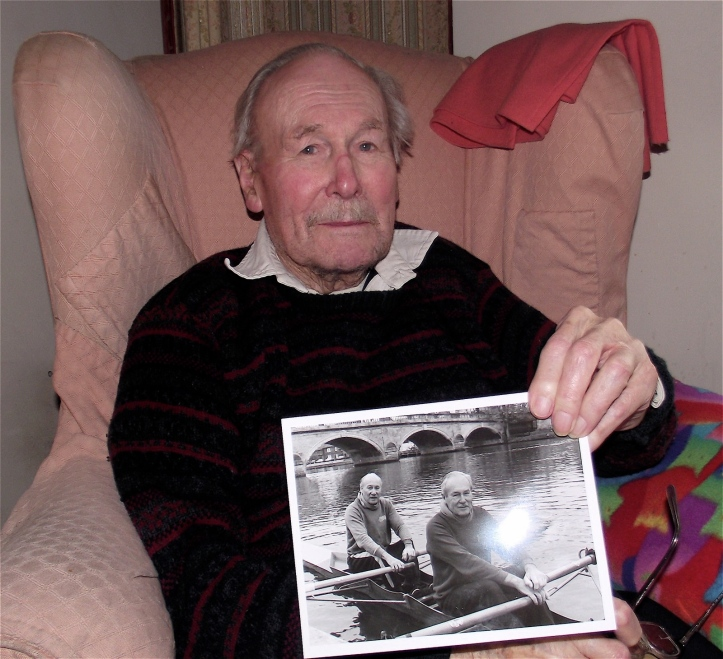 Richard Hylton-Smith photographed in 2013 at the age of 100. He is holding a photograph taken on his 90th birthday in 2002 when he went rowing with his brother Ken, a former secretary of Leander.