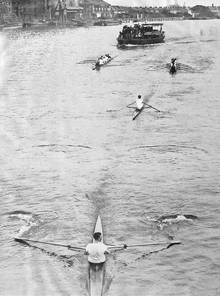 Pic 3. The 1912 Wingfield Sculls. At Hammersmith Bridge, WD Kinnear of Kensington RC leads EDP Pinks of London RC. The bowmen of the following eights are not rowing and are facing the bow, each directing their respective man, something allowed under the race rules then and now (though nowadays it is done from motorboats).