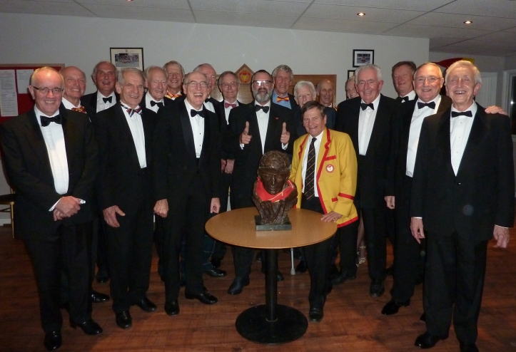 The Tideway Scullers School oarsmen at the 60's reunion in November 2015. From left to right: Mike Sweeney, Ray Tollman, Mike Muir Smith, Andy Kapica, Dave Gramolt , Rooney Massara, Mike Tebay, Chris Harris, Nick Cooper, Lionel Bailey, Willy Almand, John Russell, Arnold Cooke, Rhona MacCallum (Captain), Bill Barry, Dave Redwood , Ken Dwan and Pat Barry. Guy Greaves (President) in blazer with bust of Lou Barry (Coach) on table.