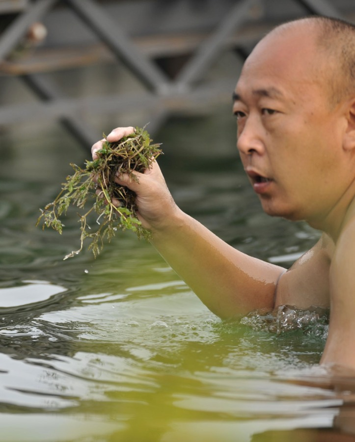 Shunyi, CHINA. Swimmer with the weed removes from the fin of GBR W2X, before the start of the women's double heat at the 2008 Olympic Regatta, Saturday, 09.08.2008 [Mandatory Credit: Peter SPURRIER, Intersport Images] 2008,Beijing,Olympic,Regatta, Games, , Rowing Course, Shun Yi Water Complex, Beijing, CHINA,