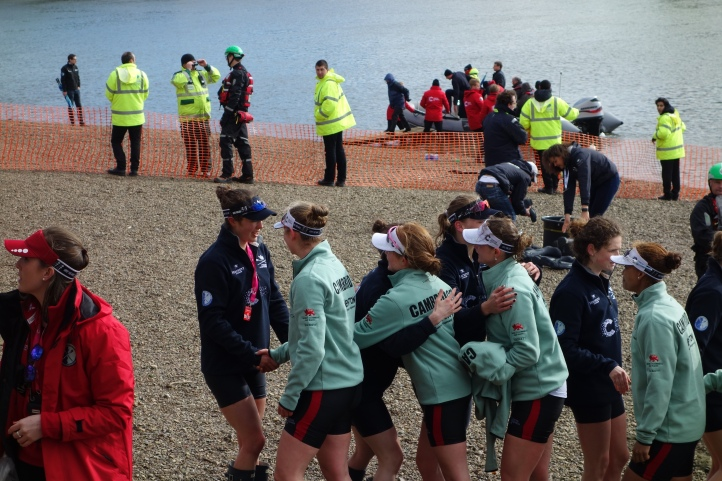 Cambridge and Oxford women shaking hands.