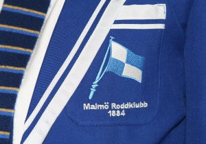Caption: Gentleman or not, ridiculous or not, the blazer of Malmö Roddklubb has the club's flag gracing its pocket.