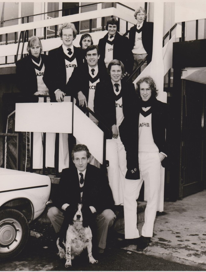 The 1976 Oxford Record Crew: from the top of the stairs: John N. Calvert (cox), David R. H. Beak (bow), Graham S. Innes (2; President), A. David Edwards (3), Stephen G. H. Plunkett (5), Kenneth C. Brown (6), A. John Wiggins (7), Andrew G. H. Baird (stroke) and R. 'Bob' S. Mason (4). Name of dog unknown.