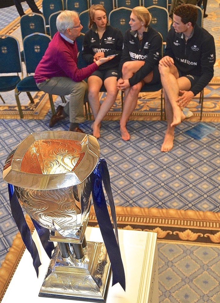 Pic 6. The 'Voice of Rowing', Robert Treharne-Jones, interviews three from the Oxford camp: women's cox, Morgan Baynham-Williams, women's number two, Emma Spruce and men's number four, Josh Bugajski. In the foreground is the women's race trophy.