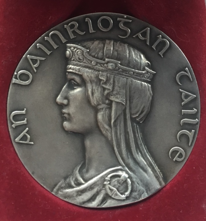 1932 Tailteann Games silver medal for rowing. The ancient Celtic Irish Queen Tailte is shown complete with Her Irish cloak, headdress and Tara brooch clasp. Dia. 50mm – hallmarked Dublin 1932. The reverse is inscribed 'Anoch Tailteann, Baile Atha Cliath. Second Prize, Rowing; it is decorated with the four provincial crests surrounding the border. 'Balie Atha Cliath' translates as 'Dublin City' where most of the events were held but the rowing events took place there only once, in 1924. In 1928, they were held in Cork and in 1932 in Drogheda.