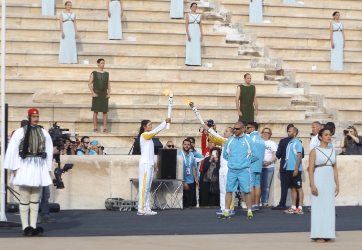 Pic 2. At the Panathenaic Stadium in Athens, the final Greek torch bearer, Katerina Nikolaidou, receives the flame from her countryman, the 1996 gymnastics champion, Ioannis Melisassanidis. Picture: Philip Barker.