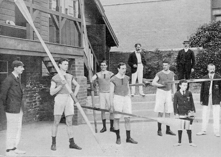 Pic 9. The Hereford Junior Four brings out the oars. On the left is the Hon. Sec, Mr. Phillips, and on the extreme right, Mr. Hammond, the Captain and Coach.