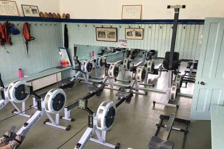 Picture 2: Our erg room, complete with photos of old Henley crews. The hooks on the wall suggest that this was once a changing room; I believe it used to be for the lower men's boats. Photo: CL, with an iPhone 6 and VSCO.
