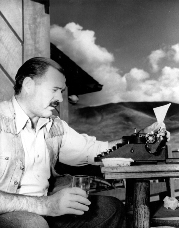Hemingway working at the typewriter, glass in hand.