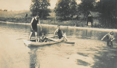 "From left to right: Hemingway, sister ""Sunny"" rowing the boat, family friend Paul Haase and in the water, Ursula. The picture was taken in September 1915 at Walloon Lake. From Hemingway Family Scrapbook at the Clarke Historical Library."