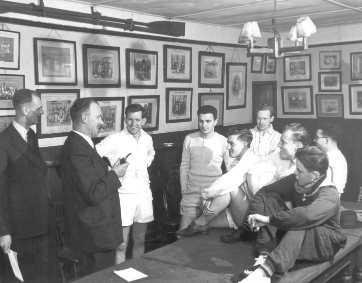 Pic 1. The bar and clubroom of the Hammersmith, West London based Kensington Rowing Club in the late 1950s. The subject of this article, Henri Benardout, is at the back, wearing glasses. Also mentioned is Jimmy Pigden, nearest to the camera on the right, and John Dixon, sitting between Jimmy and Henri.