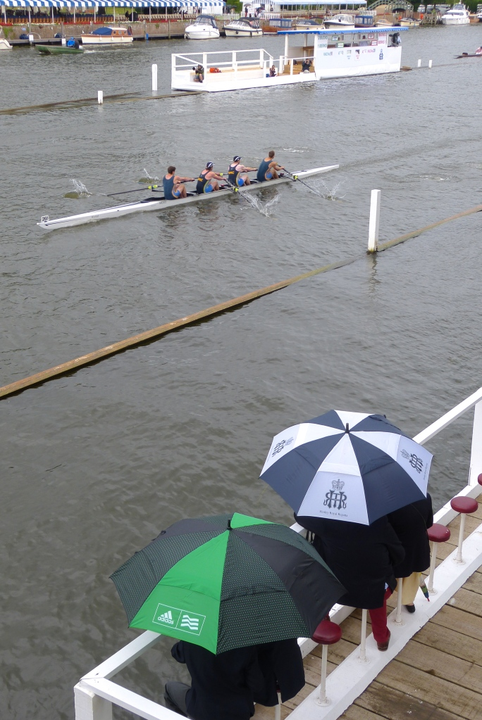 It was not a pair of pink socks or a club blazer that was the 'must have' accessory for Henley Wednesday, it was in fact a large and sturdy umbrella. Here, some die-hards watch Nottingham Rowing Club in their defeat by Thames RC home in the Wyfold Challenge Cup, the event for club coxless fours.