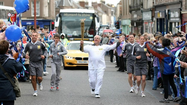 Jim Brown carries the Olympic flame on 12 June 2012. Picture: itv.com