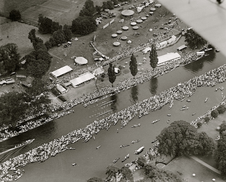 Back to the early 1920s, a view of an eights race at the 1923 Regatta passing the Stewards' Enclosure. Behind Stewards' is the funfair. Photo by Aerofilms Collection via 'A History of Britain From Above'.