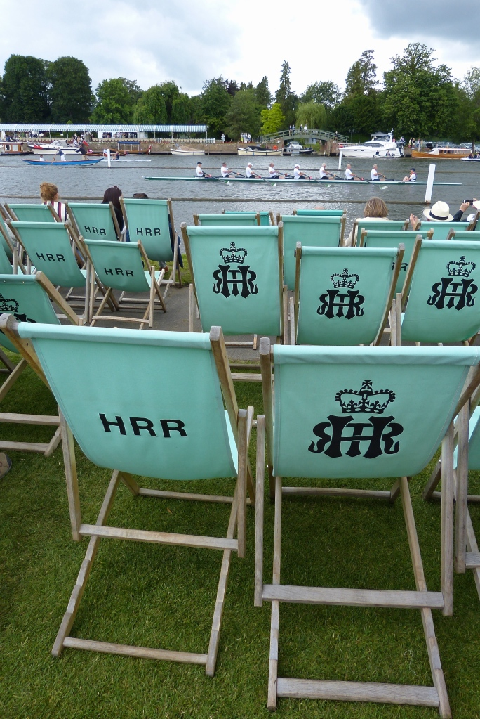 A row past during the tea interval by the Hong Kong and China Rowing Association to mark 40 years since Hong Kong crews first rowed at Henley Royal Regatta. New deck chairs now have the Regatta logo replacing the simple letters 'HRR' and this increases their desirability as 'souvenirs'. There are doubtful legends about individuals dismantling chairs and smuggling them out, one piece at a time. There are also tales of complete chairs being taken out by river.