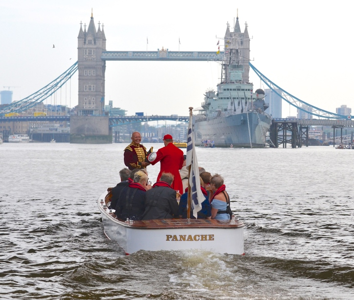 The umpire's launch heads to the marshalling area around the permanently moored HMS Belfast, just below Tower Bridge. Robert is in the purple and gold of the Fishmongers' Bargemaster while the man in Doggett's scarlet is Robert's old Henley, National Championships and Home International partner, Martin Spencer.