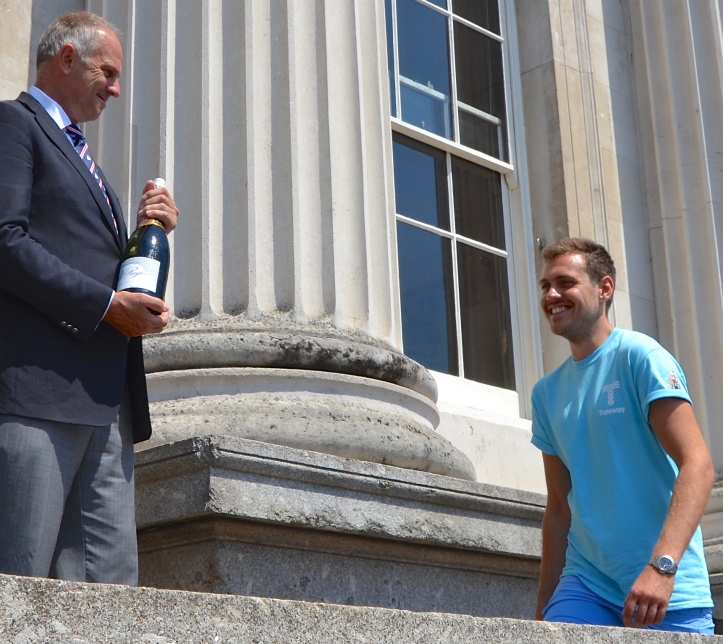 Ben Folkard is presented with Champagne and a watch from sponsors Harold Pinchbeck by Steve Redgrave. This small victory presentation on the balcony of Fishmongers' Hall is only a couple of years old, replacing what little ceremony there was at the finish at Cadogan Pier. Ben's Doggett's costume will now be made for him and he will first wear it when presented at a dinner at Fishmongers' Hall in November.