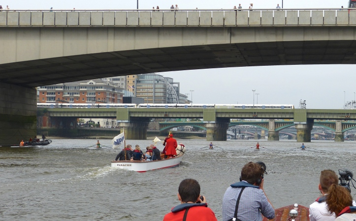 The 302nd Doggett's Coat and Badge passes under London Bridge and is underway. From left to right (south bank to north bank) is Flynn (Orange), McCarthy (Green), Anderson (Dark Blue), Berry (Red) and Folkard (Light Blue).