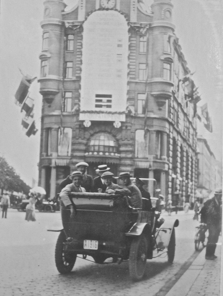A car full of celebrating Leander men is parked under a rowing results board which was affixed to the department store, Nordiska Kompaniet ('The Nordic Company').