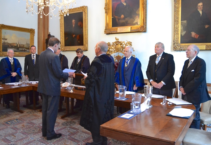 In the Court Room, Daniel Walker takes the oath at the Court of Admission in front of the Master (obscured), his Wardens and the other officers.