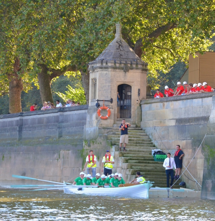 Watched by the Lord's crew (in red), the Commons crew (in green) goes afloat from Black Rod's Steps. 'Black Rod' is, in theory, responsible for maintaining the buildings, services, and security of Parliament. His steps are a reminder of the time when travelling by river was faster, safer and more comfortable than attempting to use the unsatisfactory roads.