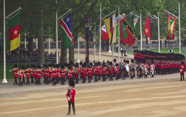 Bandsmen of the Irish Guards arrive for the Trooping the Colour. They are distinguished from the Grenadier, Coldstream, Scots and Welsh Guards by the blue plumes in their bearskins. Also, on closer inspection, their buttons are arranged in fives and they have shamrocks on their collars. The distinctive saffron kilts of the pipers are also a clue.