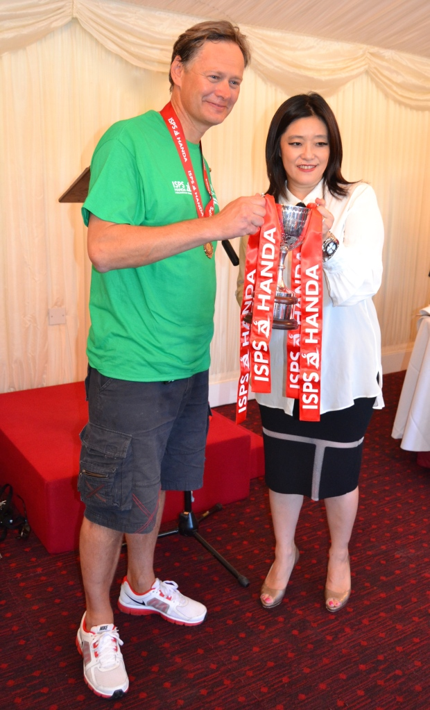 The leader of the victorious Commons team, Dr Matthew Offord MP, accepts the race trophy from Midori Miyazaki, a representative of Dr Haruhisa Handa, Chairman of the International Sports Promotion Society, sponsor of the Parliamentary Boat Race.
