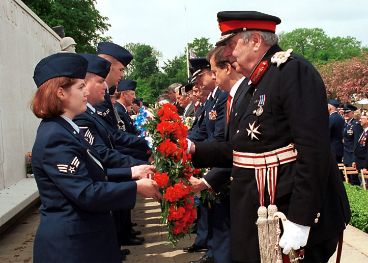 010528-F-2021R-017 Senior Airman Rebecca A. Baucum (left) passes a wreath to Her Majesty's Lord Lieutenant of Cambridgeshire James Crowden during the Madingley Memorial Day Commemorative Service on May 28, 2001, at the Cambridge American Military Cemetery, Coton, Cambridge, England. This year marks the 57th annual memorial service honoring the American servicemen and women who are buried here and those listed on the Wall of the Missing. The cemetery was dedicated on July 16, 1956, as the only permanent American World War II cemetery in the British Isles. Baucum is attached to the 48th Communication Squadron, 48th Fighter Wing, RAF Lakenheath. DoD photo by Airman 1st Class Joanna E. Reihle, U.S. Air Force. (Released)