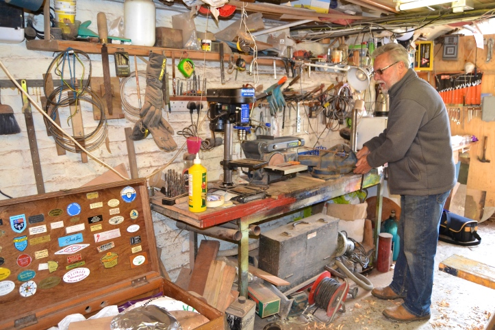 Bill at one of his workbenches. Note one of his tool boxes in the bottom left with a nice collection of boat maker's plates in the lid.