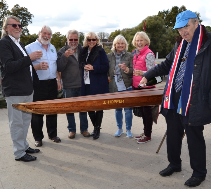 "Clive Radley (right) rechristens the ""J. Hopper"". Roger Bean, who originally rescued the boat from an uncertain future and did some initial restoration is second from the left. Bill Colley, who has now got the scull as close as possible to its original state, is third from the left."