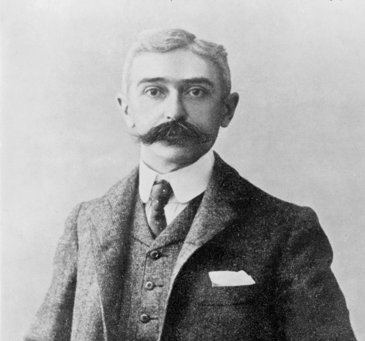 Baron Pierre de Coubertin, keen sculler and founder of the modern Olympic Movement, possibly holding a small dog under his nose.