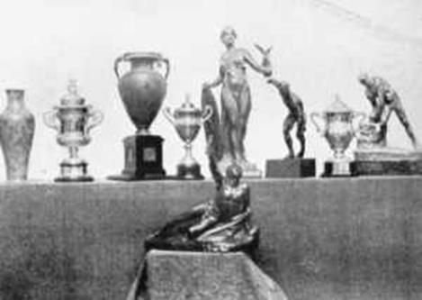 Some of the challenge cups and trophies presented at the 1908 Olympic Games. The cycling and rowing trophies in the centre and The Greek Trophy for the Marathon Race, presented to Johnny Hayes to the fore.