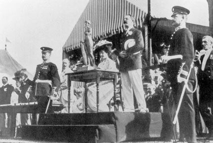 Speech by Lord Desborough of Taplow, IOC member, during the medal ceremony for rowing in Henley-on-Thames. The Brunetta Statuette can be seen on the table in front of Lord and Lady Desborough. Photo: IOC/Olympic Museum collections.
