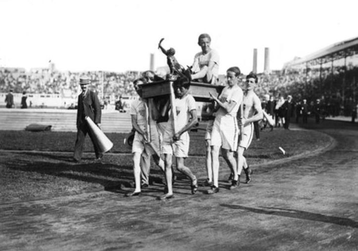 U.S. athlete Johnny Hayes finished second in the 26 miles 385 yards marathon but was declared the winner after Italian Dorando Pietri was disqualified after receiving assistance from the race umpires inside the Olympic Stadium. In the above photograph, Hayes and his trophy are carried on a table by his teammates after his victory. You can watch the finish of the race here.