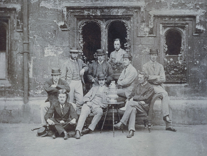 The 1867 Brasenose Head of the River Eight. Woodgate is seated on the right contemplating the trophy.
