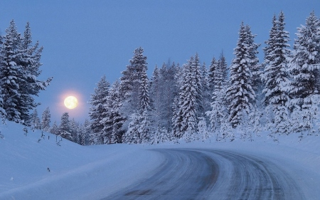 Moon over snowy country road